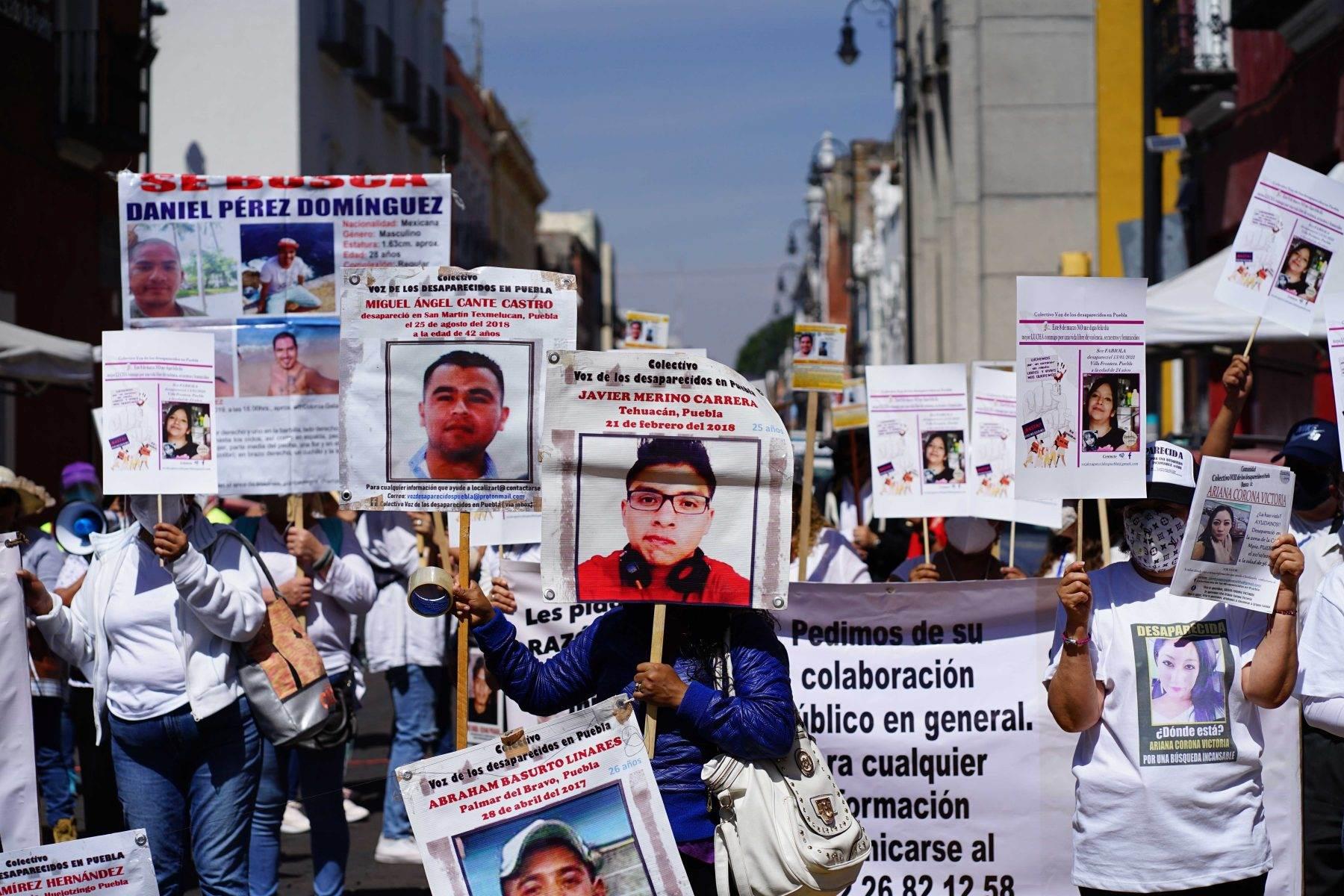 Familiares de personas desaparecidas portan carteles con los rostros de las víctimas.
