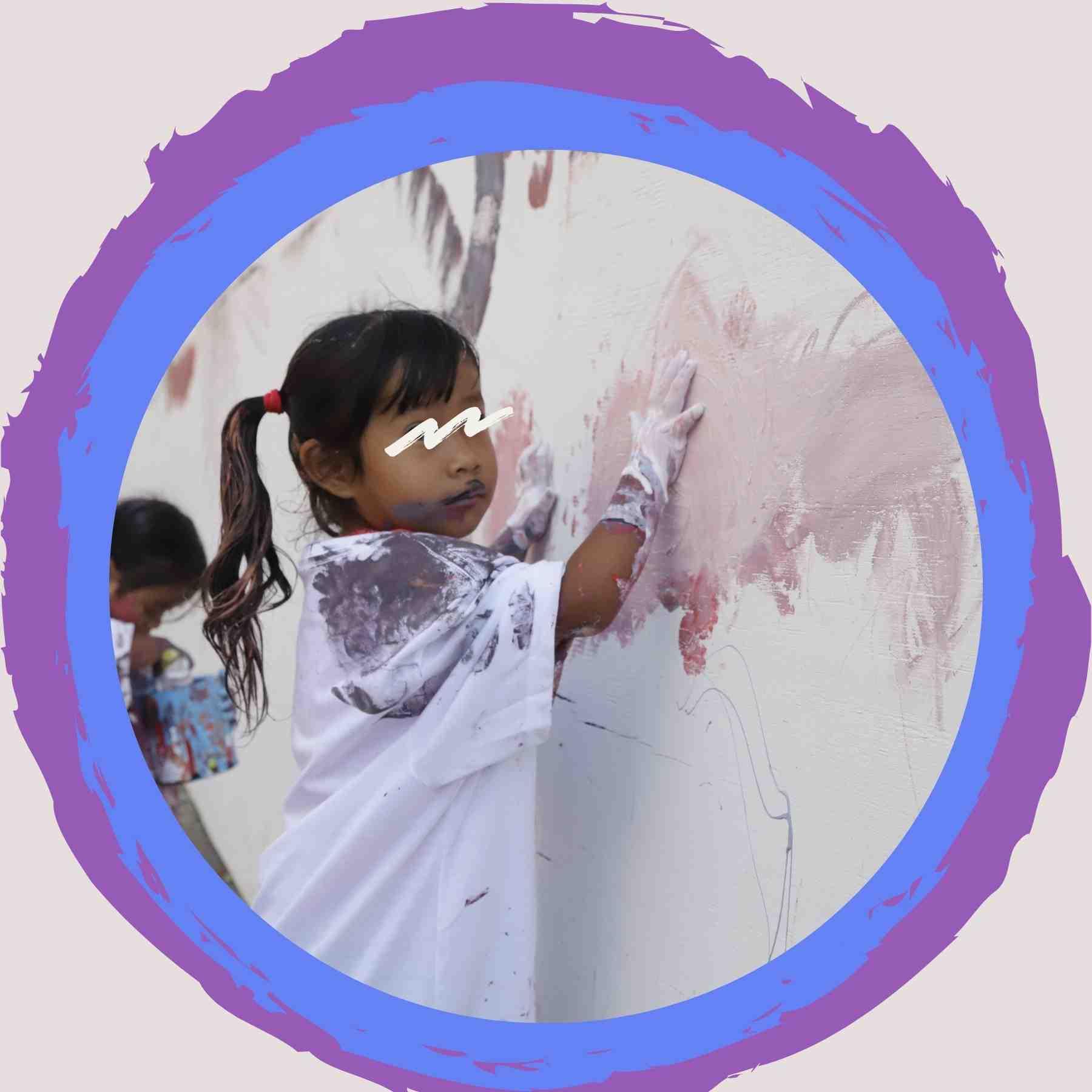 niña pintando un mural